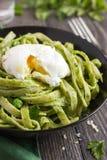 Tagliatellepasta med pesto för spenat och för gröna ärtor tjuvjagade ägget Royaltyfri Bild
