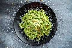 Tagliatellepasta med pestosås, sörjer muttrar och parmesan på den svarta plattan arkivfoto