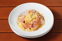 Tagliatelli carbanara italian cuisine on plate rustic kitchen table background Stock Photos