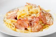 Tagliatelli carbanara italian cuisine on plate rustic kitchen table background Stock Images
