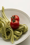 Tagliatelli pasta and fresh tomatoes Stock Photography