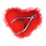 Tagliatori di chiodo sul cuore di rosso della peluche Immagini Stock