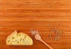 Tagliere con il cucchiaio di sale himalayano, dei grani del grano e del Br Fotografia Stock Libera da Diritti