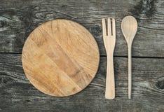 Tagliere con il cucchiaio e forcella su fondo di legno rustico Immagine Stock
