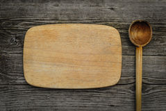 Tagliere con il cucchiaio su fondo di legno rustico Immagine Stock