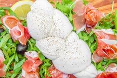 Tagliere con il prosciutto e la mozzarella del razzo Fotografie Stock