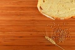 Tagliere con l'orecchio, i grani e la fetta del grano di pane Fotografia Stock Libera da Diritti