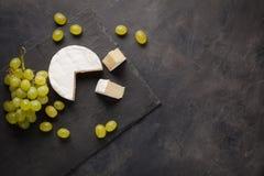 Tagliere del formaggio del camembert e dell'uva bianca su fondo di pietra scuro Dalla vista superiore con lo spazio della copia immagine stock libera da diritti