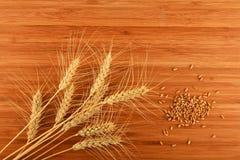 Tagliere di bambù di legno con nove orecchie e grani del grano Immagine Stock Libera da Diritti
