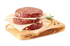 Tagliere di legno con la pila di tortini crudi dell'hamburger del manzo su bianco Fotografia Stock