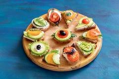 Tagliere di legno rotondo della cucina con i panini con le verdure, il formaggio e le erbe fotografia stock