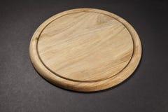 Tagliere di legno rotondo su grey Fotografia Stock