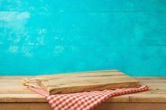 Tagliere di legno vuoto sul tavolo da cucina con la tovaglia più immagine stock libera da diritti