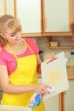 Tagliere di plastica di pulizia della donna con lo straccio Fotografia Stock