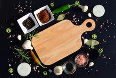 Tagliere e pepe vuoti, foglia di alloro, rosmarino, cipolle, sale himalayano, olio d'oliva, salsa di soia su un backg nero Fotografia Stock