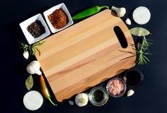 Tagliere e pepe vuoti, foglia di alloro, rosmarino, cipolle, sale himalayano, olio d'oliva, salsa di soia su un backg nero Fotografia Stock Libera da Diritti