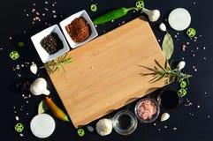 Tagliere e pepe vuoti, foglia di alloro, rosmarino, cipolle, sale himalayano, olio d'oliva, salsa di soia su un backg nero Immagine Stock
