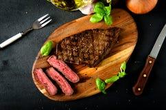 Tagliere raro affettato della spezia del basilico della bistecca Fotografie Stock