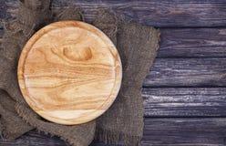 Tagliere rotondo sul vecchio fondo di legno di struttura Vista superiore immagine stock libera da diritti