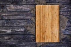 Tagliere su fondo di legno scuro, vista superiore Immagini Stock
