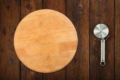 Taglierina d'acciaio della pizza a fondo di legno fotografia stock libera da diritti