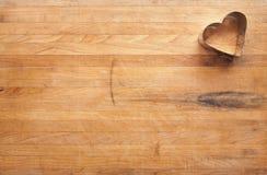 Taglierina del biscotto del cuore sul blocchetto di macellaio consumato Immagini Stock