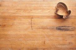 Taglierina del biscotto del guanto sul blocchetto di macellaio consumato Fotografia Stock