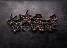 Taglierine dei biscotti di Natale - albero di Natale, cervo, stella, forma di MANN del pan di zenzero con le fave di cacao fotografia stock