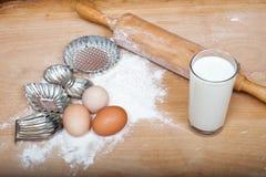 Taglierine del biscotto ed ingredienti della pasta sulla tavola di legno Immagine Stock