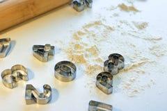 Taglierine del biscotto sotto forma di numeri sulla tavola con farina Cucinando i biscotti a casa fotografie stock libere da diritti