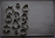 taglierine Natale-di tema del biscotto Taglierine del biscotto di Natale su fondo nero Scheda di festa Fotografia Stock