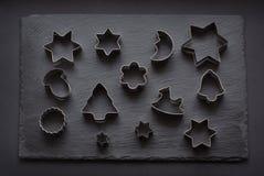 taglierine Natale-di tema del biscotto Taglierine del biscotto di Natale sul nero Scheda di festa Fotografia Stock