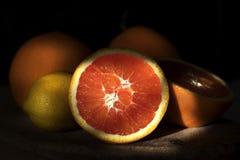 Taglio arancio rosso succoso a metà che si trova sulla luce solare fotografia stock
