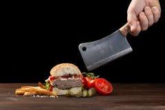 Taglio casalingo dell'hamburger in mezzo primo piano con manzo, il pomodoro, la lattuga, il formaggio e le patate fritte sulla ta immagini stock