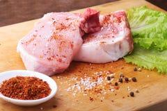 Taglio crudo su un tagliere rustico con sale, pepe e la smerigliatrice per le spezie Per lo spazio della copia Vista superiore immagini stock
