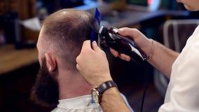 Taglio dei capelli con l'aiuto della macchina e del pettine del regolatore Punto di vista posteriore del cliente maschio barbuto, archivi video