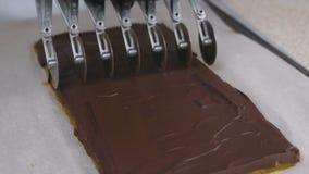 Taglio dei materiali da otturazione per la pralina delle caramelle di cioccolato con i semi dell'albicocca facendo uso della tagl video d archivio