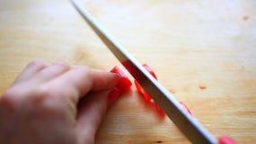 Taglio dei peperoni roventi sul bordo di legno Fine in su archivi video