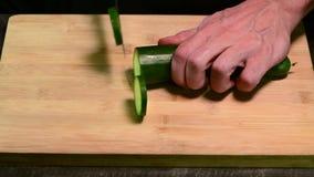 Taglio del cetriolo con il coltello sul bordo di legno archivi video