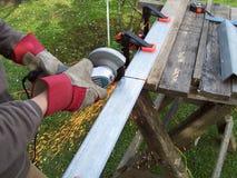 Taglio del materiale con una smerigliatrice di angolo Fotografie Stock