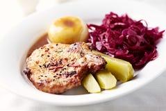 Taglio dell'arrosto di maiale con gli gnocchi della patata ed il cavolo rosso fotografie stock