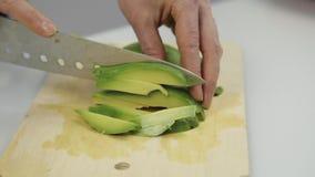 Taglio dell'avocado nei pezzi Affettatura dei frutti per lattuga archivi video