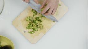Taglio dell'avocado nei pezzi Affettatura dei frutti per lattuga Vista superiore 4K video d archivio