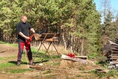 Taglio dell'uomo con la motosega elettrica Lavoro sull'azienda agricola Preparazione del legno per riscaldare Il taglialegna lavo immagine stock libera da diritti