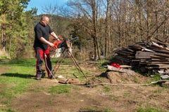 Taglio dell'uomo con la motosega elettrica Lavoro sull'azienda agricola Preparazione del legno per riscaldare Il taglialegna lavo immagini stock libere da diritti