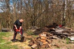 Taglio dell'uomo con la motosega elettrica Lavoro sull'azienda agricola Preparazione del legno per riscaldare Il taglialegna lavo immagini stock