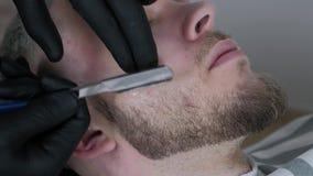 Taglio della barba con la rasatura del rasoio diritto Chiuda su di rasatura della barba nel negozio di barbiere Stile maschio del stock footage