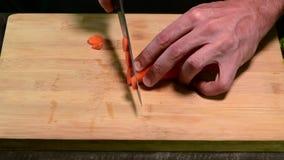 Taglio della carota con il coltello sul bordo di legno stock footage