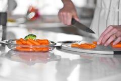 Taglio della carota nella cucina Fotografie Stock Libere da Diritti