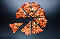 Taglio della pizza della fetta con i funghi, le olive e le salsiccie su fondo nero Vista superiore Immagini Stock Libere da Diritti